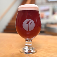 Beach Boyz is served in a tulip glass filled with a red fruity-looking beer from Lost Winds Brewing Company