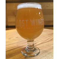 Stuck in Cabo is served in a chalice glass filled with a light bodied unfiltered looking beer from Lost Winds Brewing in San Clemente